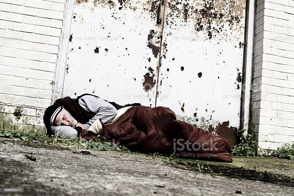 homeless man sleeping in doorway stock photo