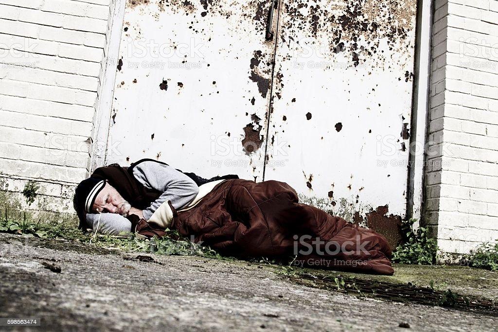homeless man sleeping in doorway stock photo