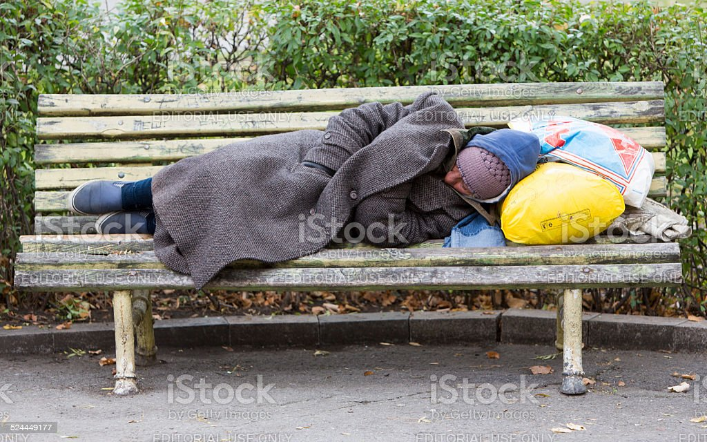 Homeless man sleeping on a bench stock photo