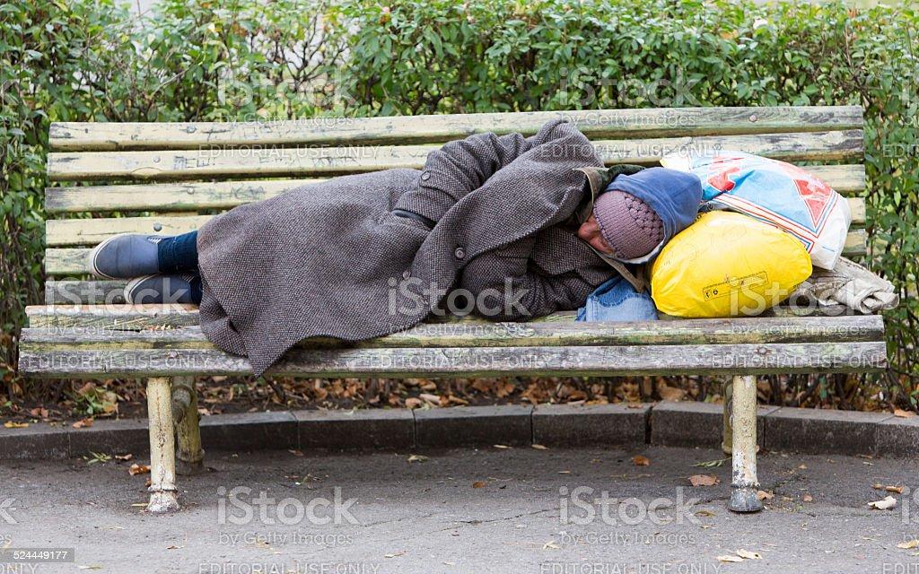 Homeless man sleeping on a bench stock photo