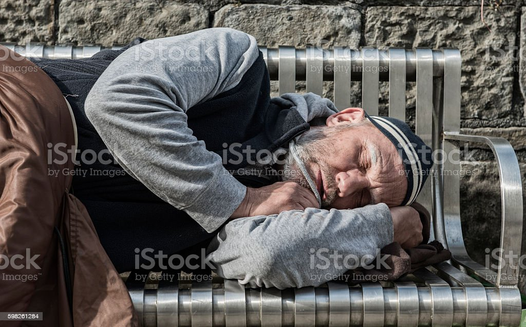 Homeless man sleeping with old blankets stock photo