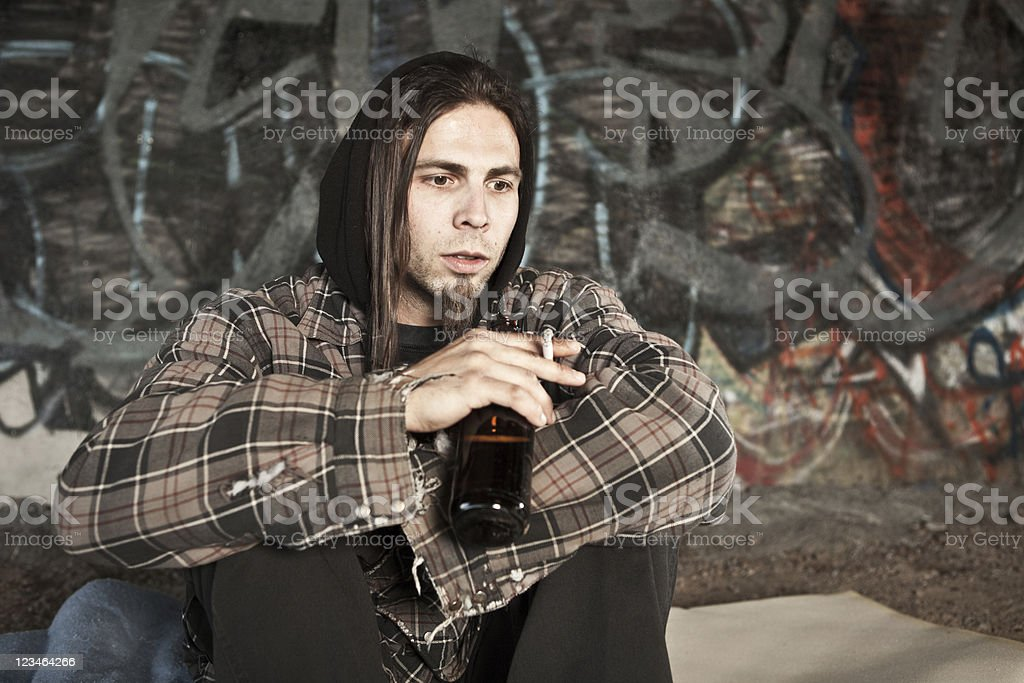 Homeless man smoking cigarrette and drinking beer stock photo