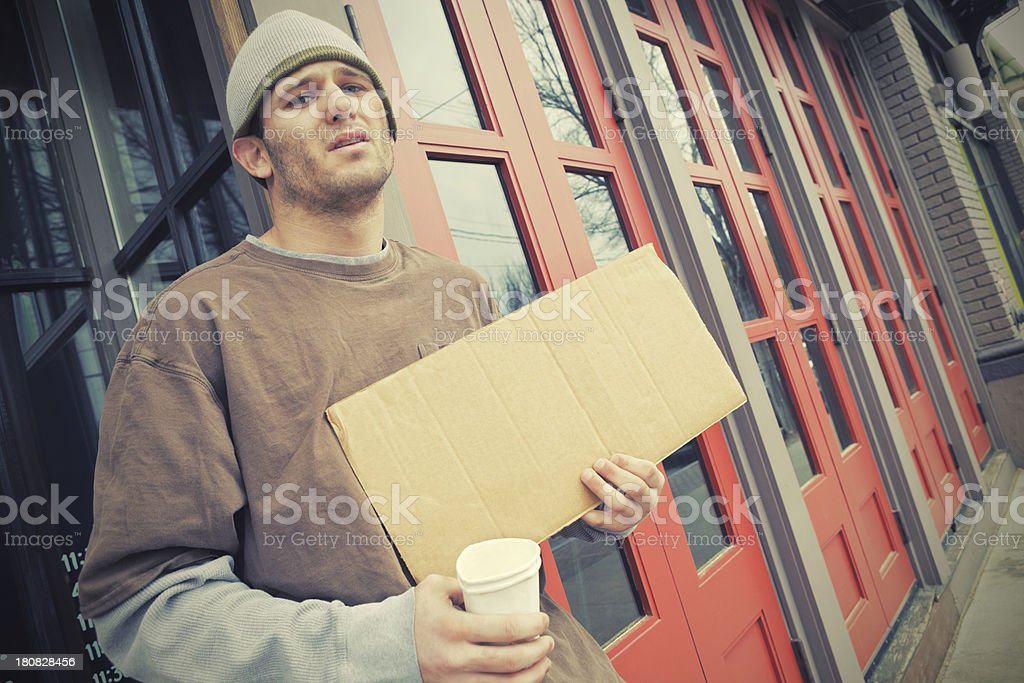 Homeless man with cardboard sign asking for donations royalty-free stock photo