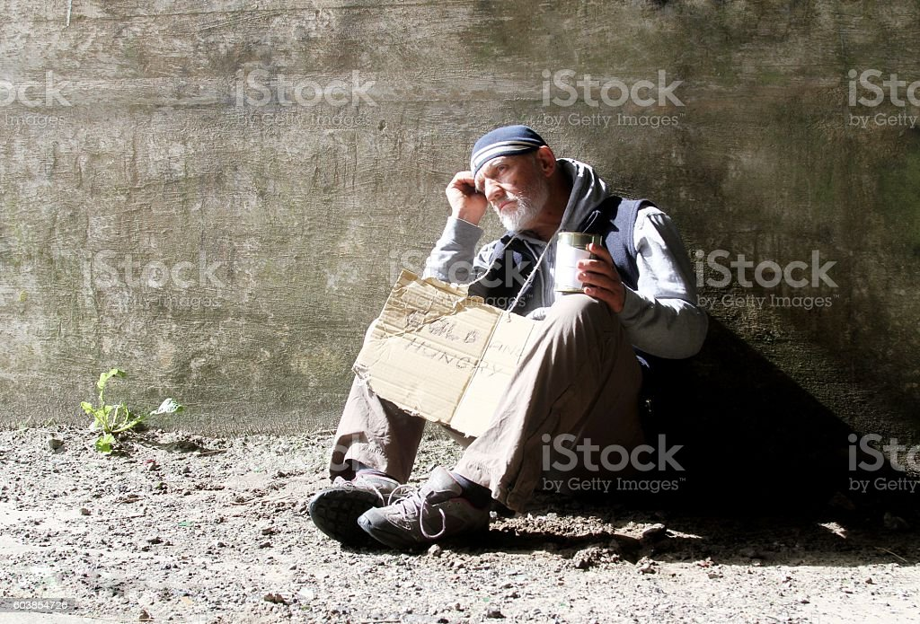 homeless man with cardboard sign stock photo