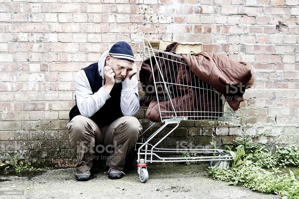 Homeless man with possessions in a shopping cart stock photo