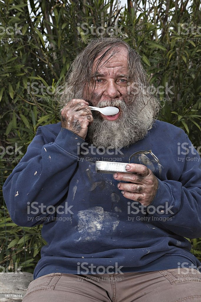 Homeless Person Eats Sardines stock photo