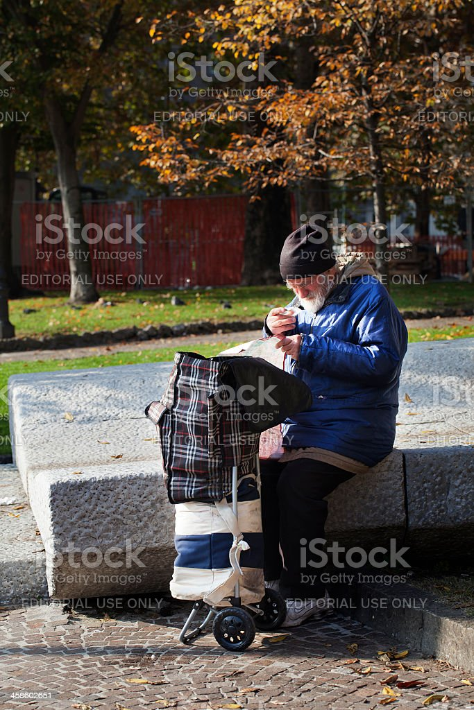 Homeless Reading a Newspaper Outdoors in Milan stock photo