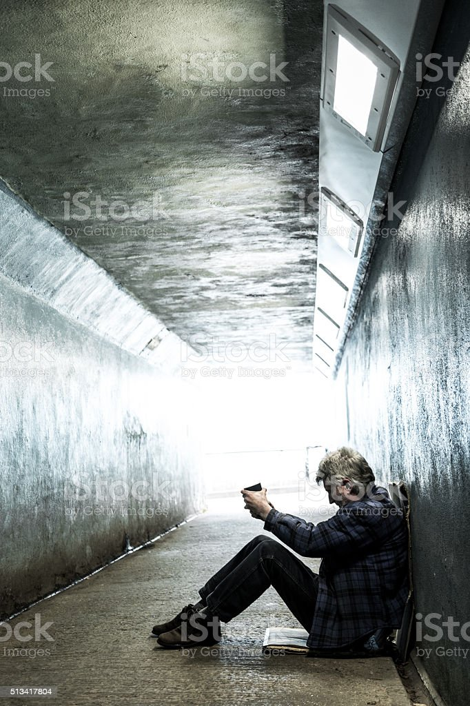 Homeless senior adult man sitting and begging in subway tunnel stock photo