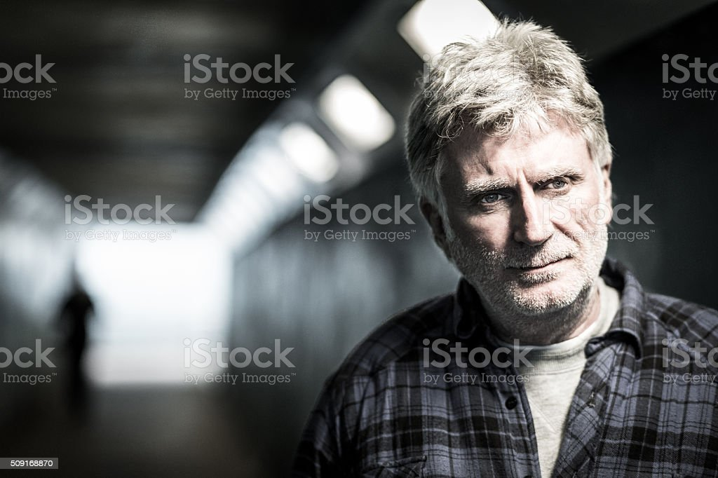 Homeless senior adult man with beard in subway tunnel stock photo