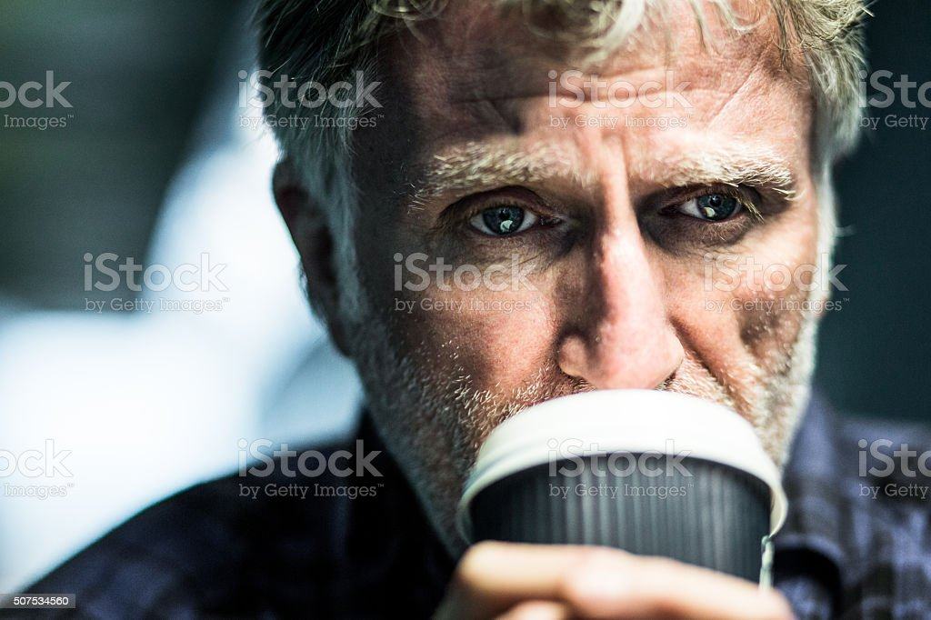 Homeless senior man begging with paper cup in subway tunnel stock photo