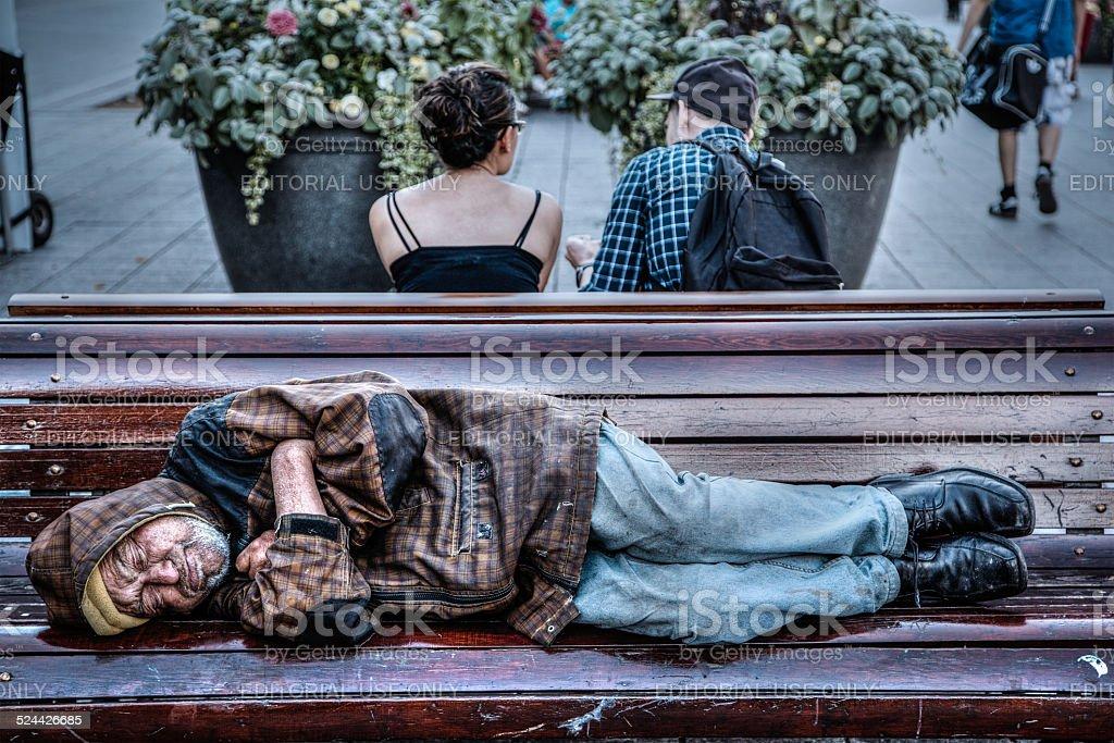 Homeless Senior Man Sleeping on Park Bench stock photo
