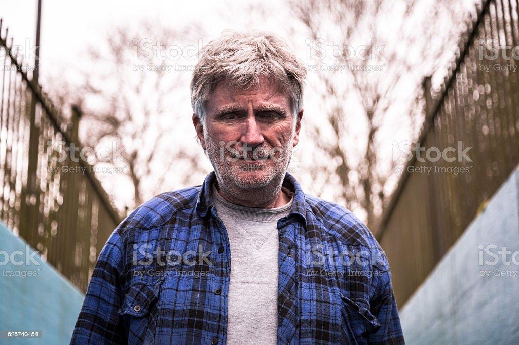Homeless senior man with grey beard looking at camera stock photo