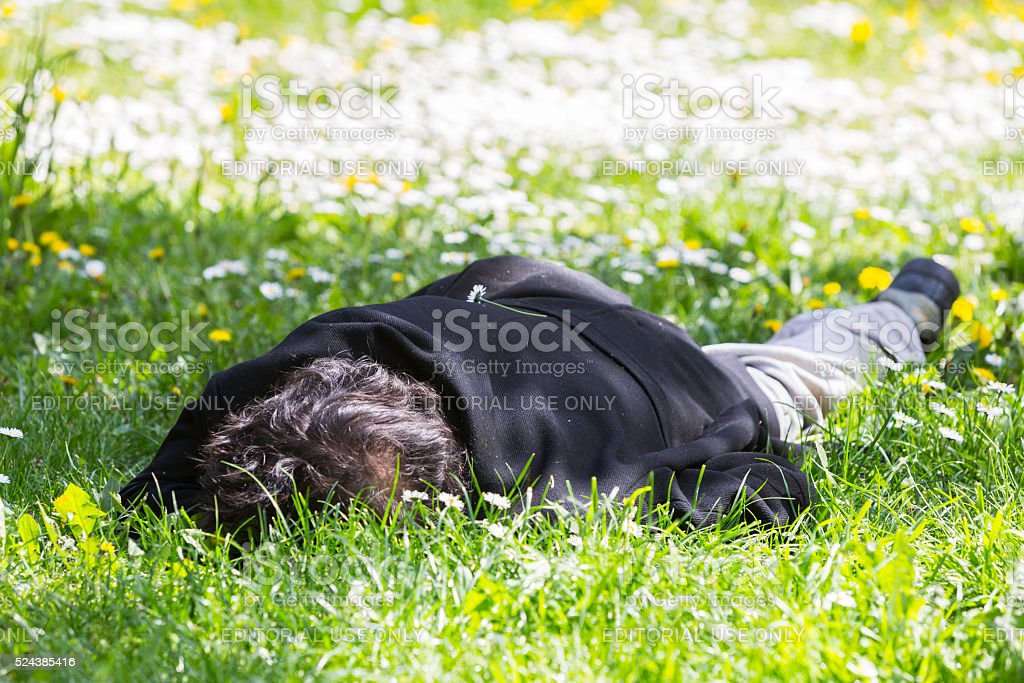 Homeless sleeping in the grass stock photo