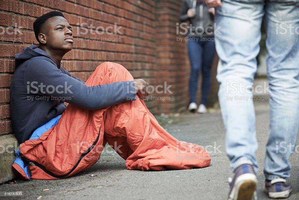 Homeless Teenage Boy In Sleeping Bag On The Street stock photo
