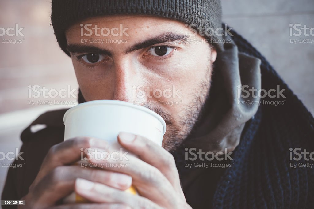 Homeless whit dirty hands drinking alone stock photo