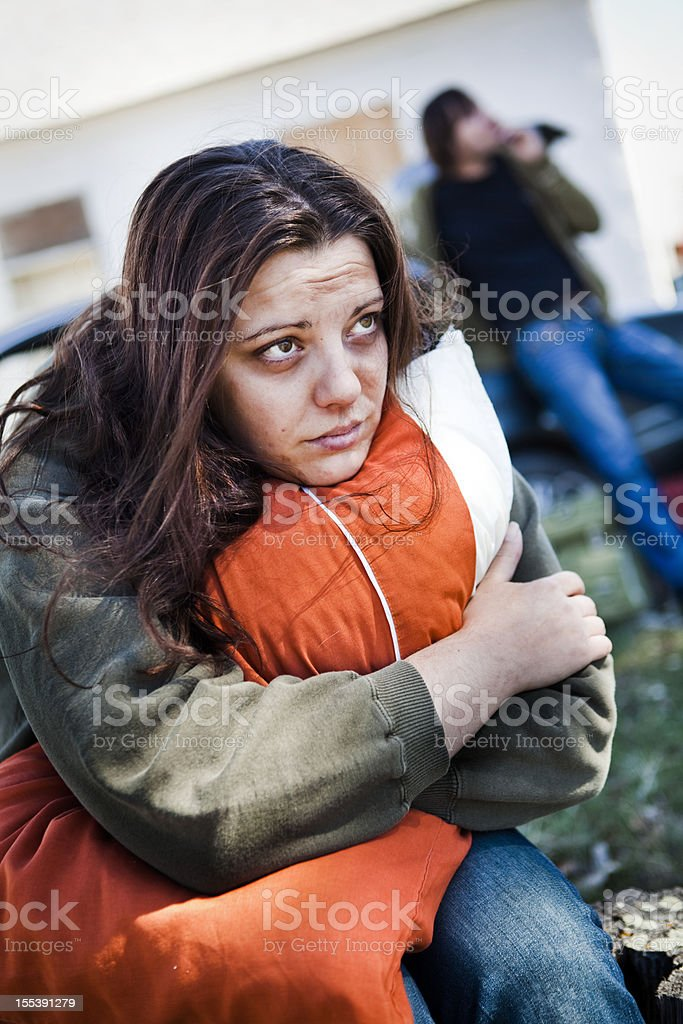 Homeless woman hugging a pillow looking worried royalty-free stock photo