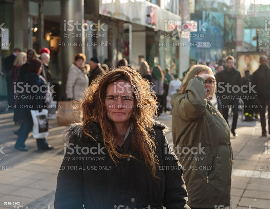 Homeless woman on city highstreet stock photo
