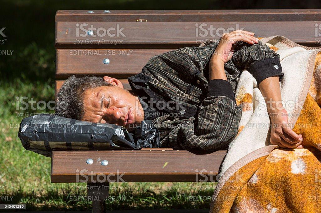 Homeless woman sleeping on a bench stock photo