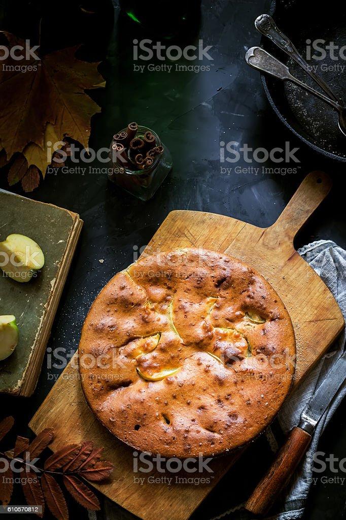Homemade apple pie in vintage iron pan on dark background. stock photo