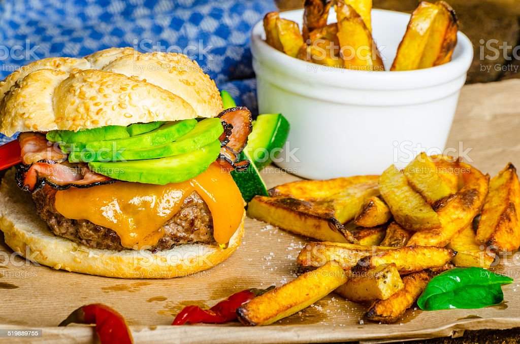 Homemade avocado burger with home spicy fries stock photo