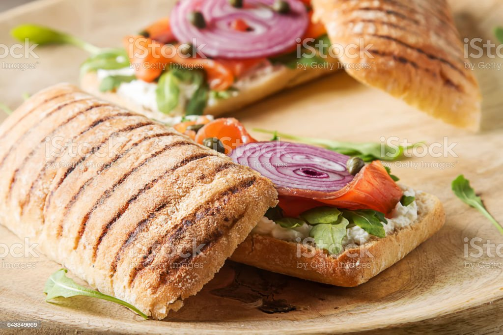 homemade baguette with smoked salmon, onions and arugula. Wooden stock photo
