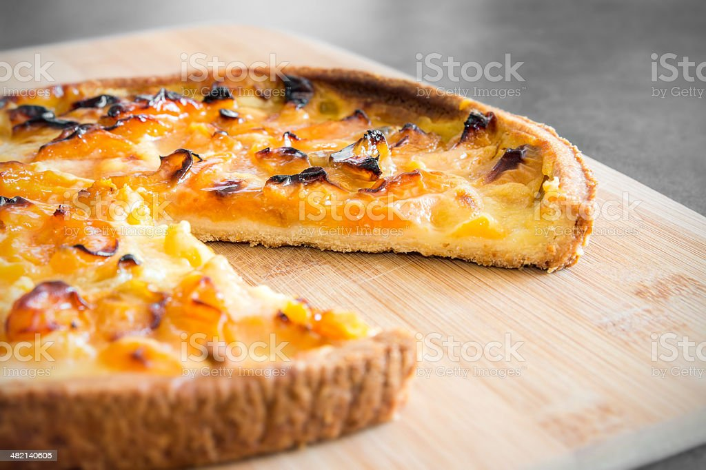 Homemade baked apricot tart on wooden cutting board stock photo