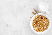 homemade baked muesli and milk on white background, top view