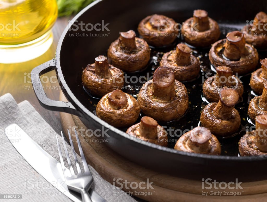 Homemade baked mushrooms in the pan on a cutting board. stock photo