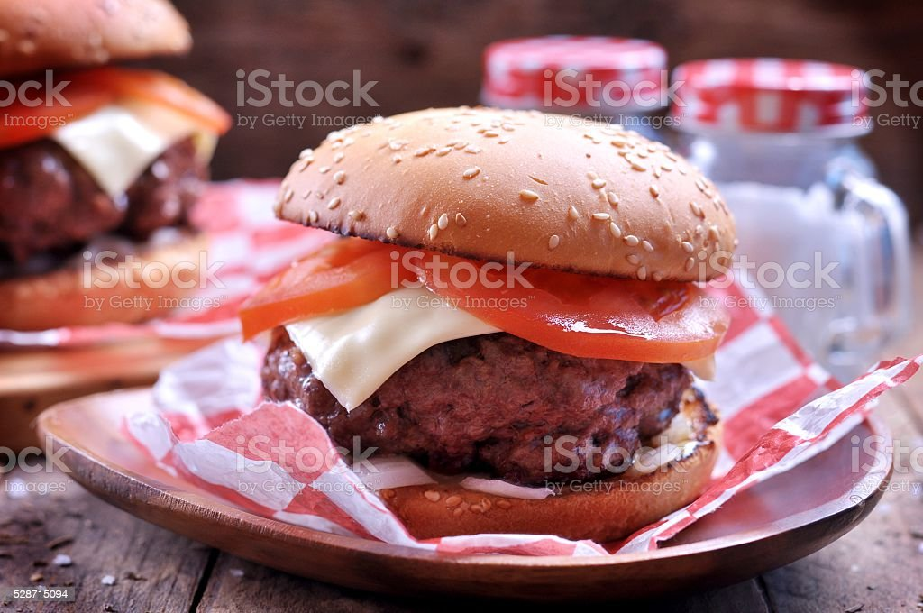 Homemade beef burger with cheese, tomato and pickled onions stock photo