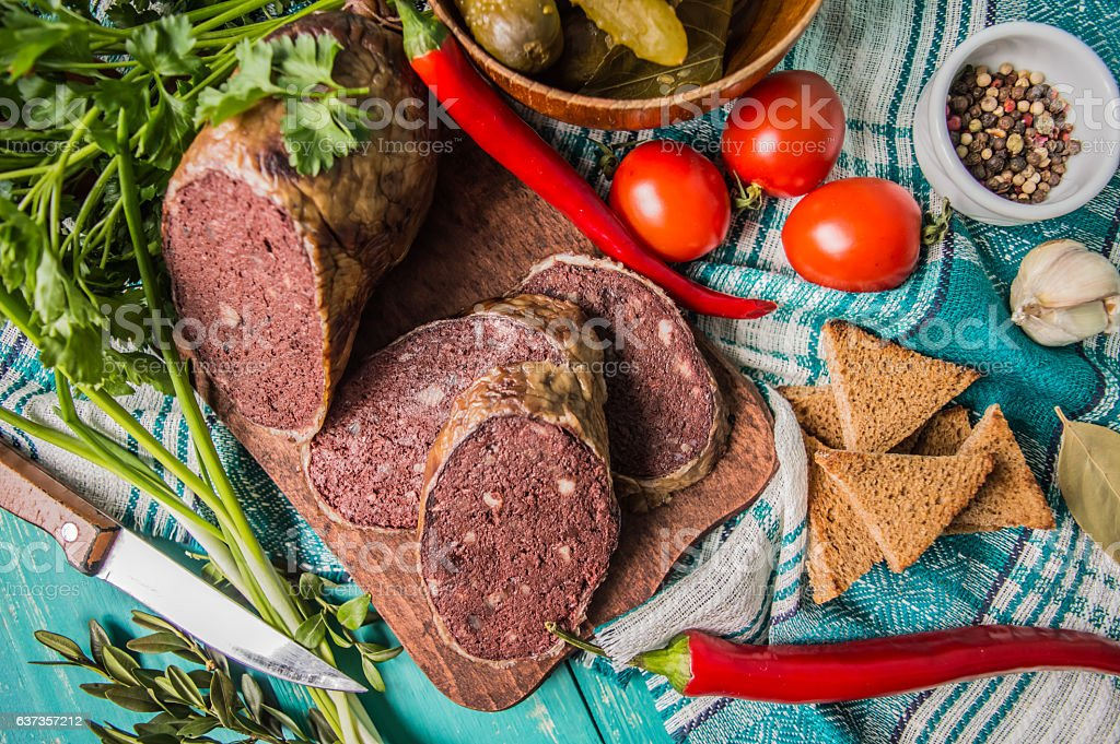 Homemade blood sausage with offal on a turquoise wooden background stock photo