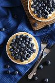 Homemade blueberry tart on black wooden table