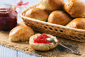 Homemade bread buns with poppy seeds and strawberry jam.