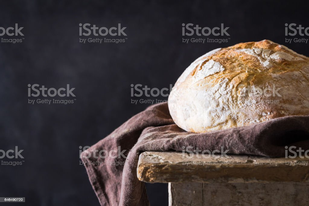 Homemade bread loaf on old table. Dark background stock photo