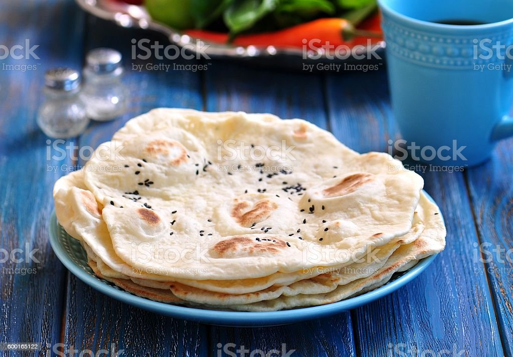Homemade bread pita bread on a blue background. stock photo