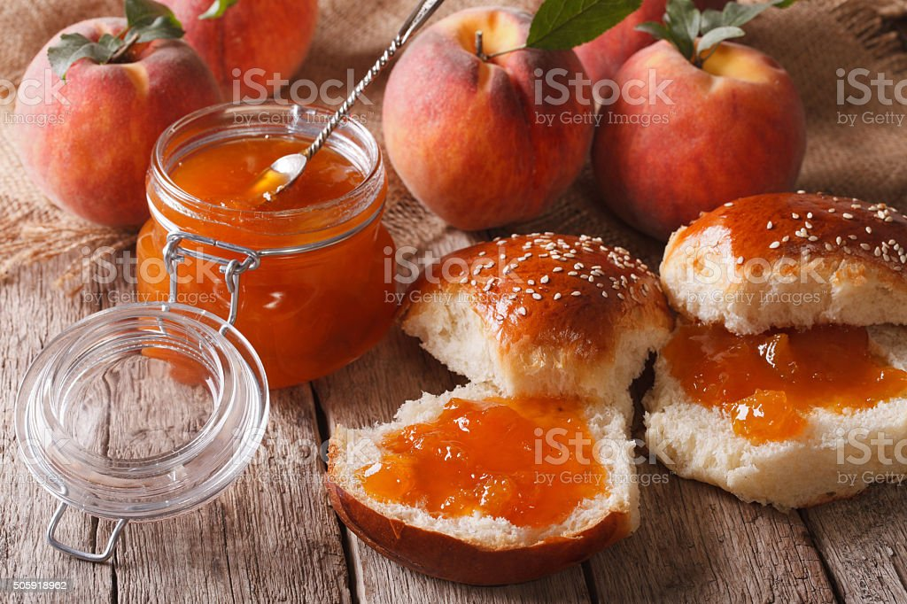 Homemade buns with peach jam close-up on the table. Horizontal stock photo
