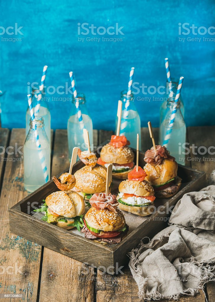 Homemade burgers in wooden tray and lemonade in bottles stock photo
