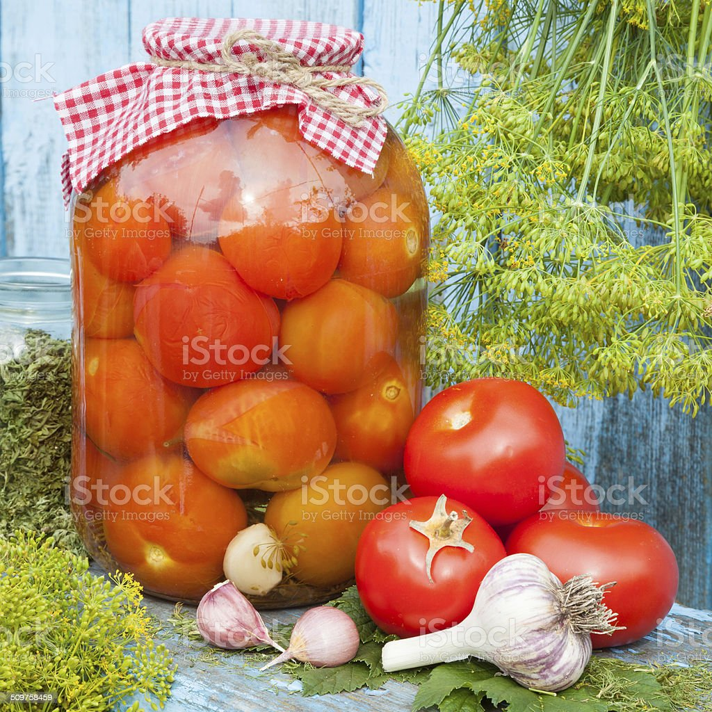 Homemade canned red tomatoes in glass jar stock photo