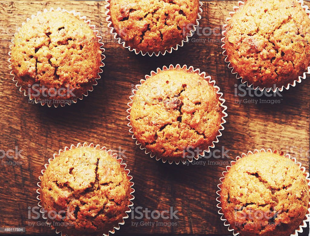 Homemade carrot muffins on brown wooden background stock photo