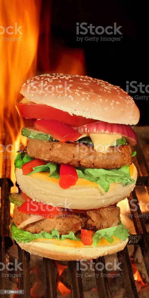 XXL Homemade Cheeseburgers On The BBQ Flaming Grill stock photo