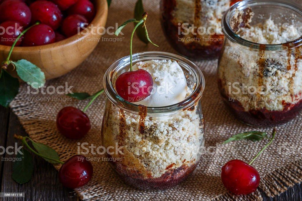 Homemade cherry crumble in glass jars. stock photo