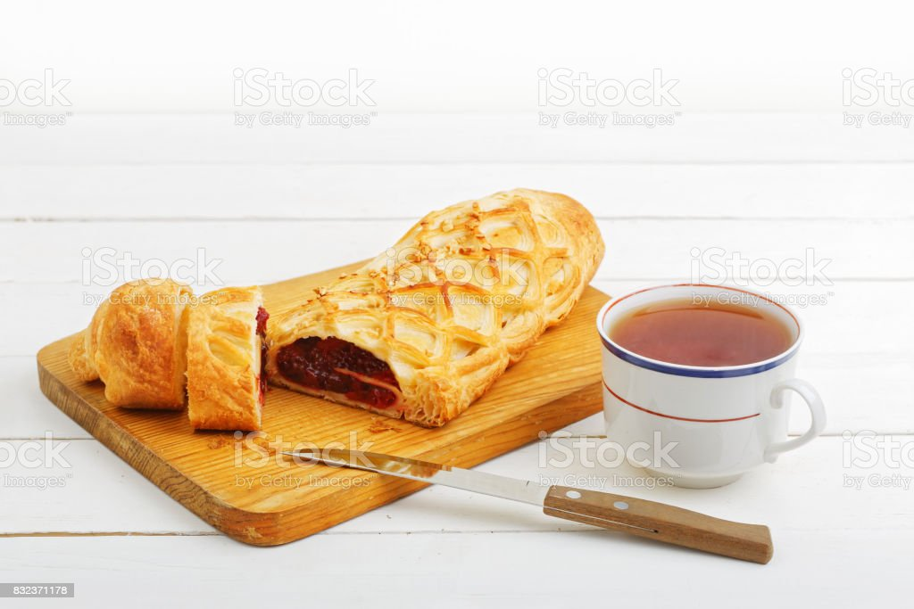 Homemade cherry strudel on a white wooden table stock photo