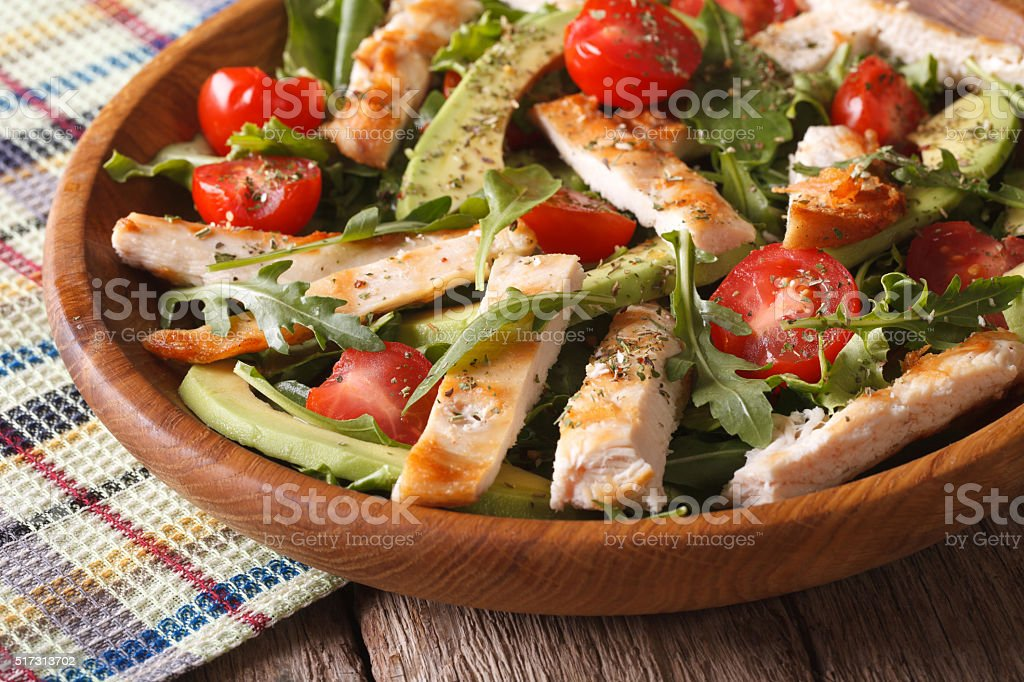 Homemade chicken salad with avocado and arugula closeup. horizontal stock photo