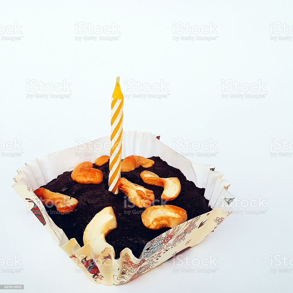 Home-made Chocolate Brownies with Cashew Nuts and a yellow candl stock photo