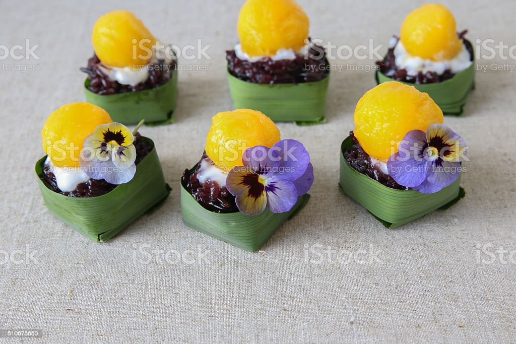 Homemade coconut sticky rice with mango in pandan leaves cup stock photo