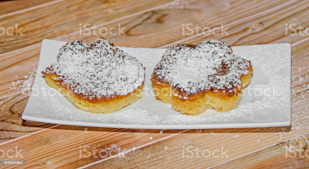 Homemade Creme brulee with powder sugar,  burnt cream, crema catalana, or Trinity cream, white plate and wood background stock photo
