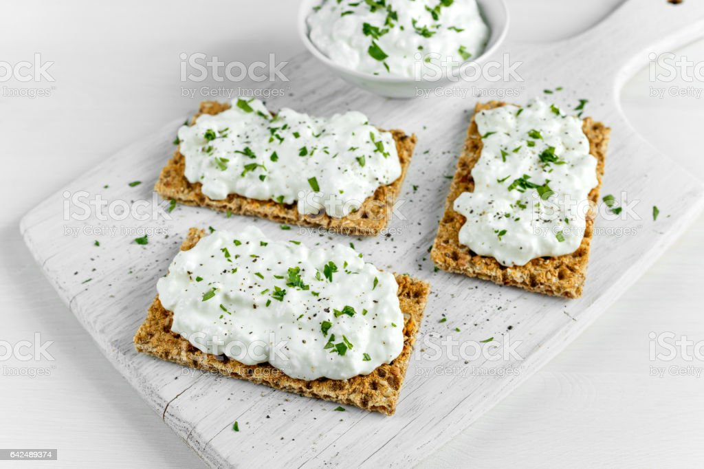 Homemade Crispbread toast with Cottage Cheese and parsley on white wooden board. stock photo