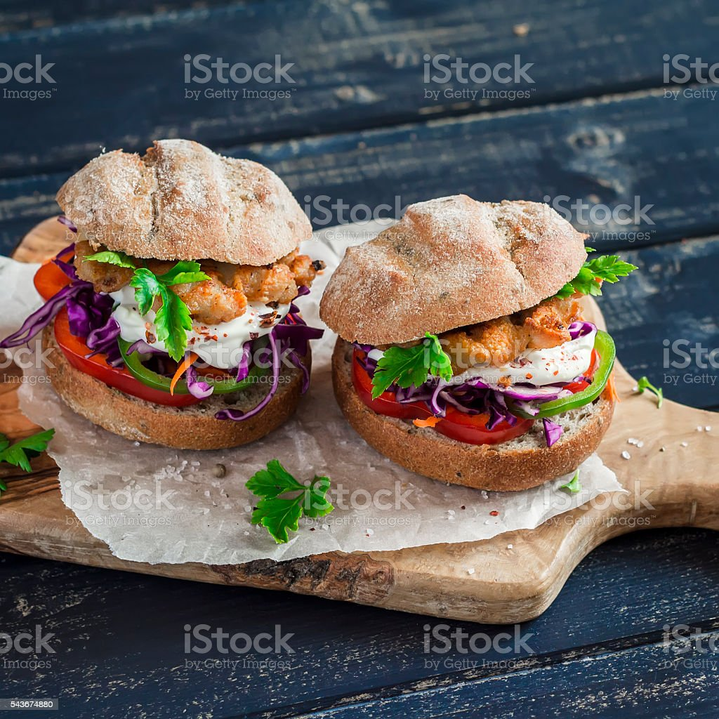 Homemade crispy fish burger on a dark rustic wooden board stock photo