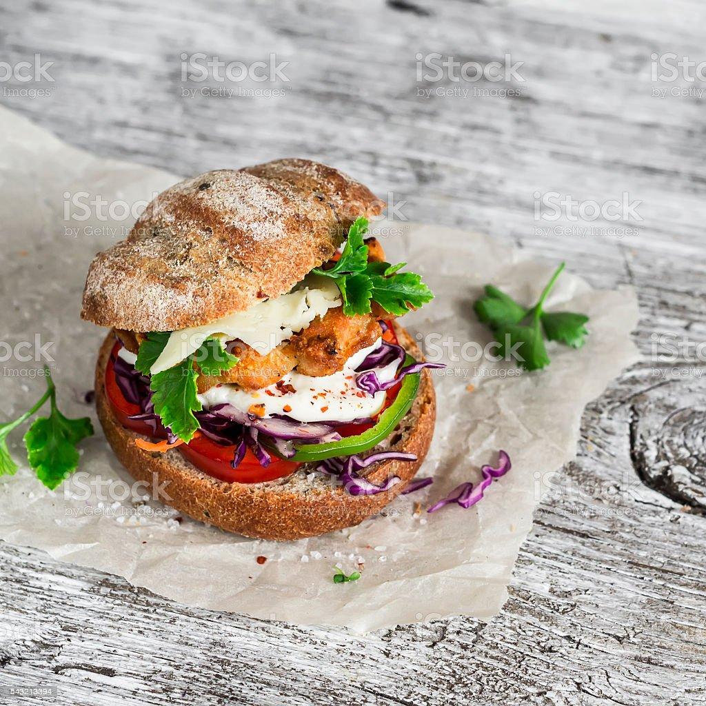 Homemade crispy fish burger on a light rustic wooden board stock photo