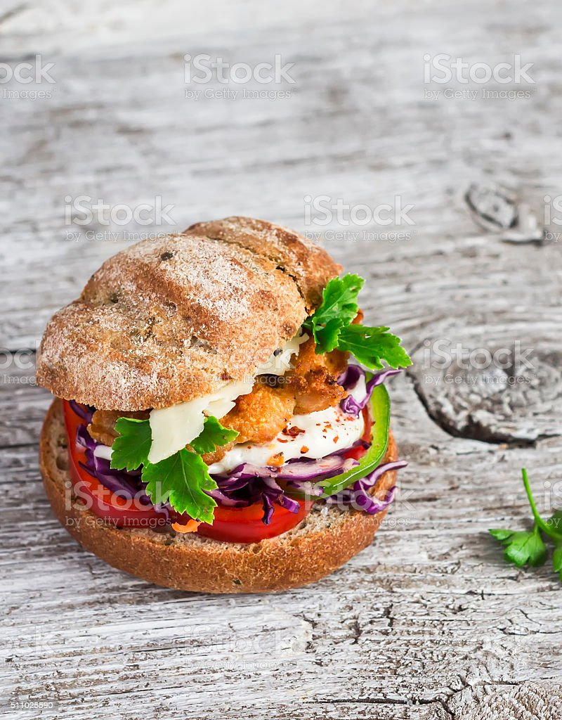 Homemade crispy fish burger on a rustic wooden board stock photo