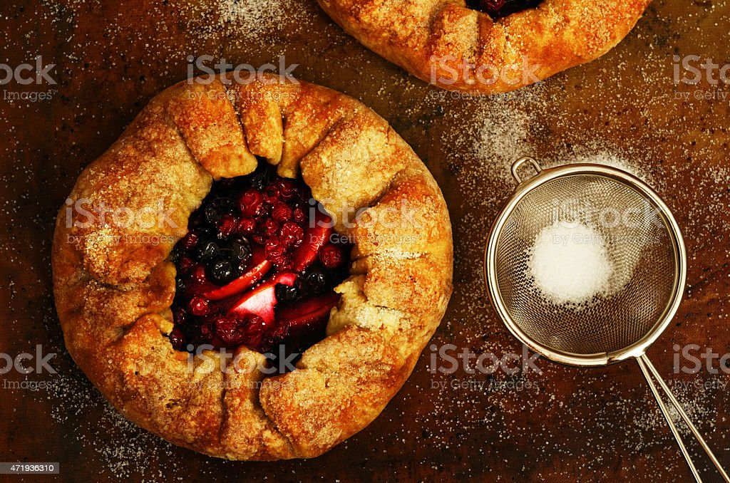 Homemade crusty pies or galette with apples and berries stock photo